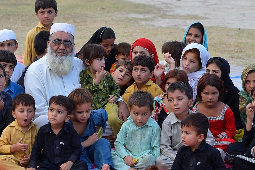 In this photograph taken on July 11, 2014, internally-displaced Pakistani resident Haji Gulzar Khan Wazir, who fled with his family following a military operation against militants in the North Waziristan tribal agency, poses for a photograph with so