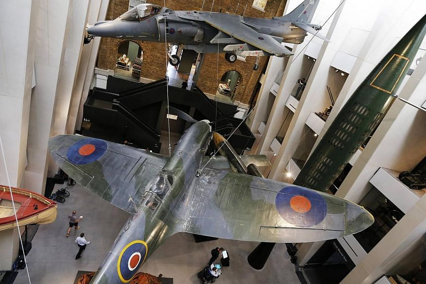 Members of the media and museum staff walk through the refurbished central atrium of the Imperial War Museum during a media preview, in central London on July 16, 2014. -- PHOTO: REUTERS