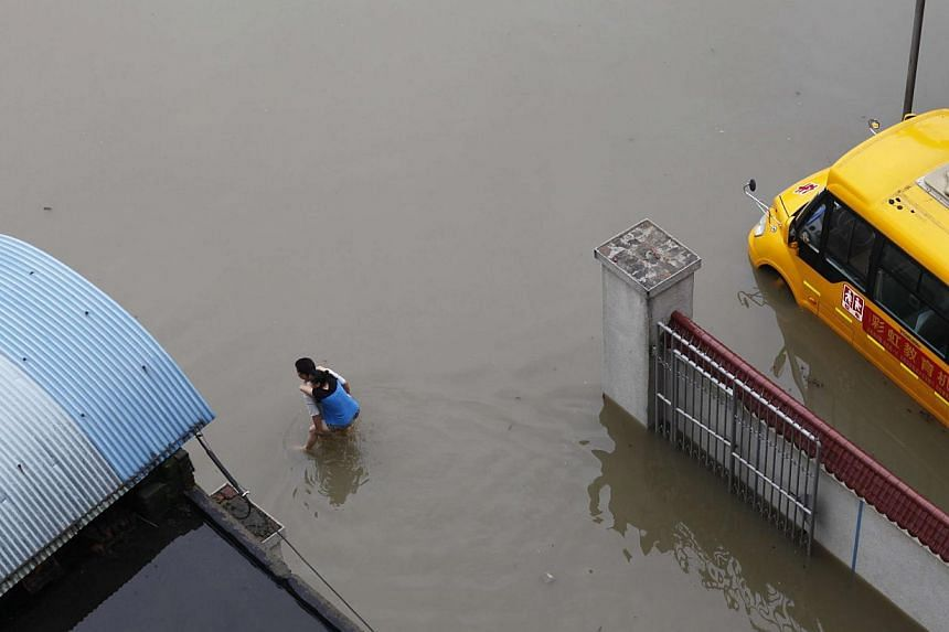 This picture taken on July 16, 2014 shows a man carrying a woman as he makes his way through a flooded area in Miluo, in central China's Hunan province.At least 20 people have died in the past week as torrential rain batters swathes of China, w