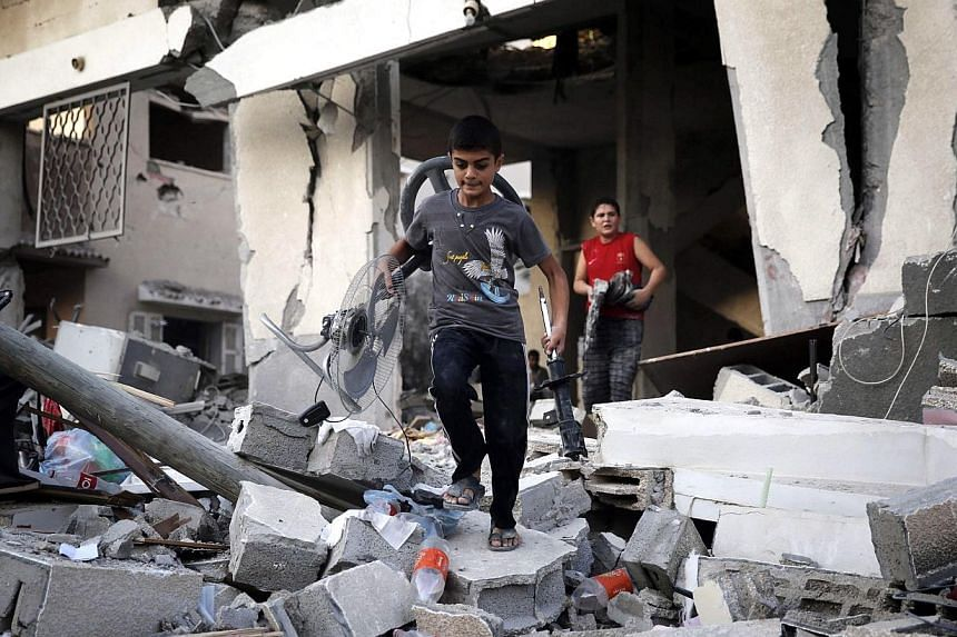 Palestinian boys salvage belongings from a damaged home, which police said was targeted in an Israeli air strike, in Gaza City on July 17, 2014.A five-hour humanitarian truce agreed by Israel and Hamas came into force on Thursday, hours after t