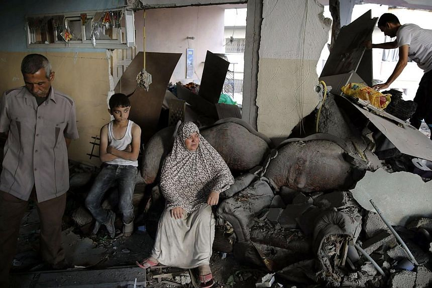 A Palestinian family gathers inside their damaged home, which police said was targeted in an Israeli air strike, in Gaza City on July 17, 2014. A five-hour humanitarian truce agreed by Israel and Hamas came into force on Thursday, hours after th