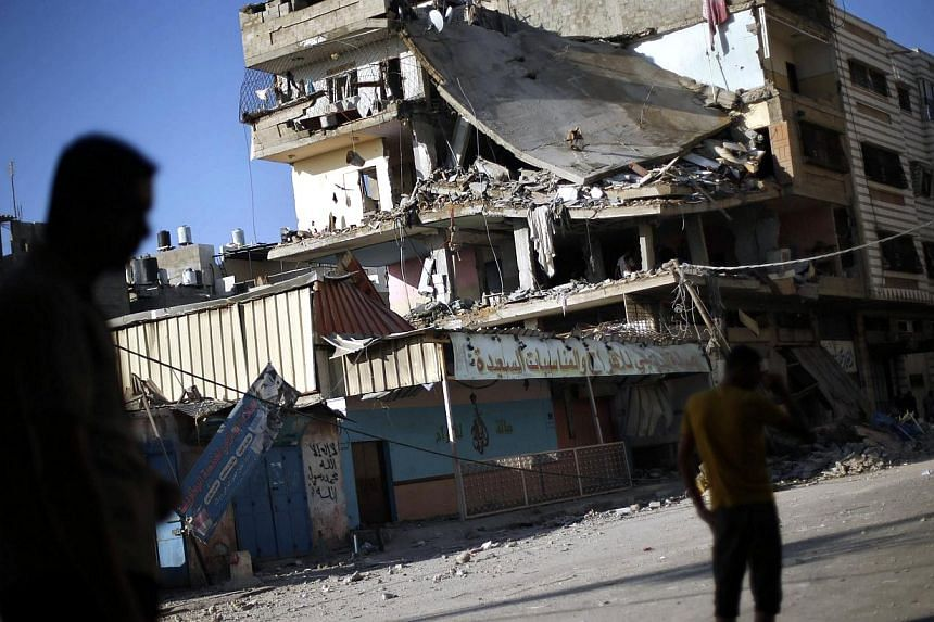 Palestinians stand next to a house which police said was targeted in an Israeli air strike in Gaza City on July 17, 2014.A five-hour humanitarian truce agreed by Israel and Hamas came into force on Thursday, hours after the Israeli military sai