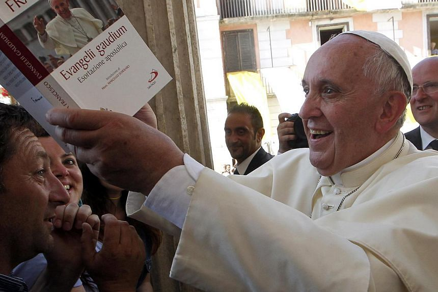 Pope Francis signs an autograph on one of his books given by a faithful, as he arrives to lead a prayer in Isernia, south of Italy,on July 5, 2014. An Italian director best known for telling complex on-screen love stories will begin shooting the