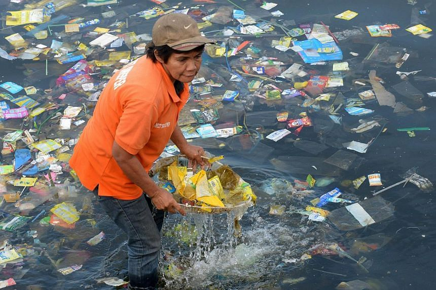 Plastic bags and other rubbish are collected from the waters of Manila Bay on July 3, 2014 during a campaign by environmental activists and volunteers calling for a ban of the use of plastic bags. -- PHOTO: AFP