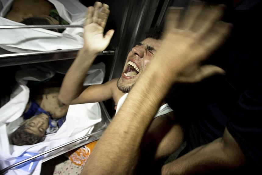 A relatives of four Palestinian boys, all from the Bakr family, mourns over the body of one of the boys at the morgue of al-Shifa hospital in Gaza City, on July 16, 2014. -- PHOTO: AFP