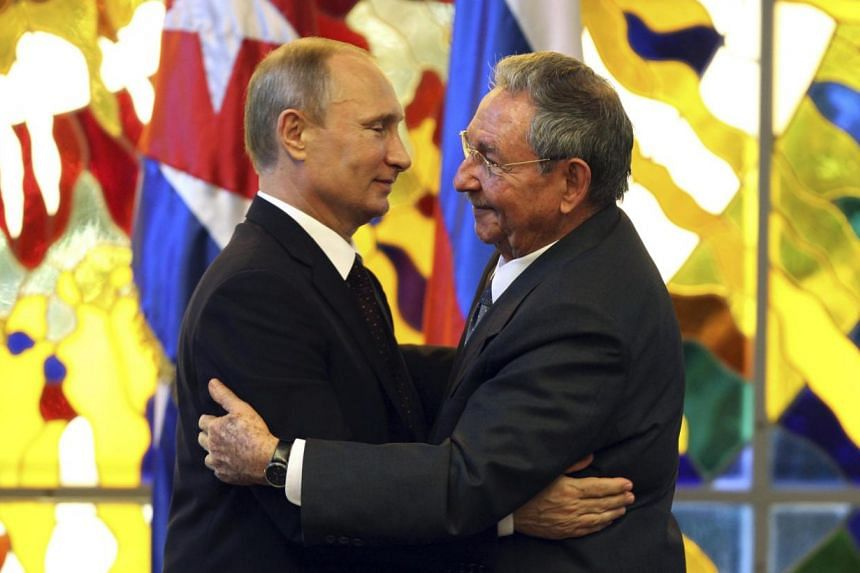 Russia's President Vladimir Putin (left) hugs Cuba's President Raul Castro after a meeting at the Revolution Palace in Havana on July 11, 2014. The visit was part of a six-day tour of Latin America for Mr Putin. -- PHOTO: REUTERS