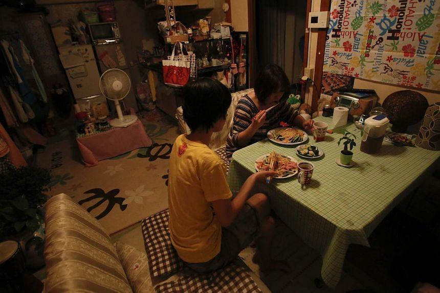 Ririko Saito and her 11-year-old daughter Yumi eat dinner together, one of only two meals they have a day in an attempt to keep household costs low, at their apartment in Tokyo on May 14, 2014. Japan's child poverty rate has hit a record high, accord