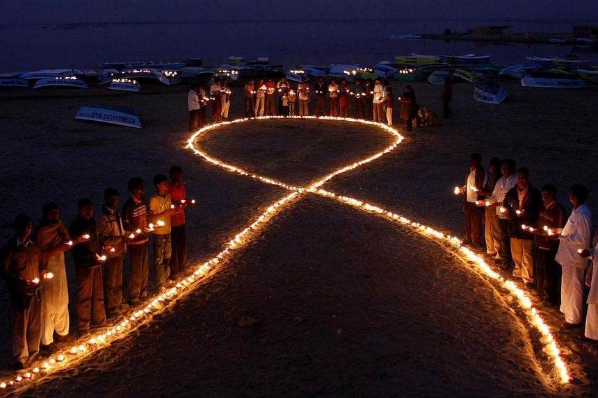A 2009 file picture shows Indian villagers holding oil lamps as they surround a huge AIDS symbol on the beach at Nalsarovar, some 60km from Ahmedabad, on the eve of World Aids Day. Many of the passengers who died when a Malaysia Airlines plane crashe