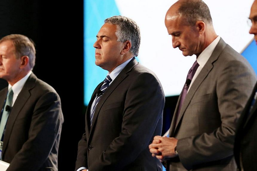 (From left) SEB Chairman Marcus Wallenberg, Treasurer of Australia Joe Hockey, GE Global Growth and Operations CEO John Rice and OECD Secretary-General Angel Gurria observe a minute of silence for the victims of Malaysia Airlines flight MH17 at the B