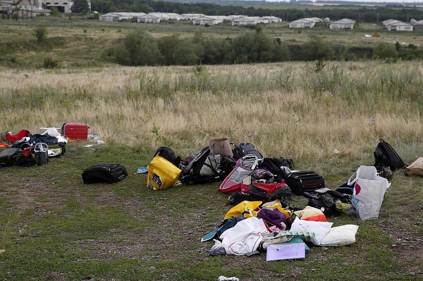 Luggage and belongings are seen near the site of Thursday's Malaysia Airlines Boeing 777 plane crash, near the settlement of Grabovo in the Donetsk region on July 18, 2014. -- PHOTO: REUTERS