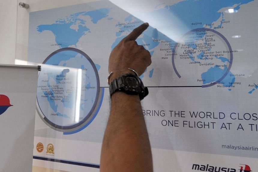A man points at a world map at a Malaysia Airlines branch office in Jakarta on July 18, 2014 after Malaysia Airlines flight MH17 was shot down over Ukraine. -- PHOTO: AFP