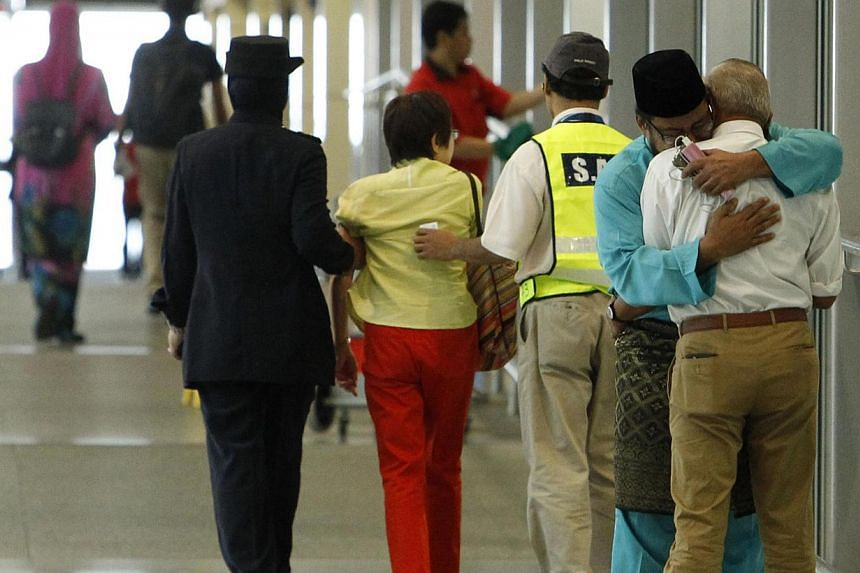 A man (in blue) whose family was onboard the Malaysia Airlines MH17 consoles another who had just arrived with her wife to receive confirmation that their daughter's family was onboard the plane, at Kuala Lumpur International Airport in Sepang on Jul