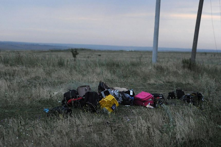 Luggages are pictured on July 17, 2014 on the site of the crash of the Malaysian airliner carrying 298 people from Amsterdam to Kuala Lumpur, near the town of Shaktarsk, in rebel-held east Ukraine. -- PHOTO: AFP