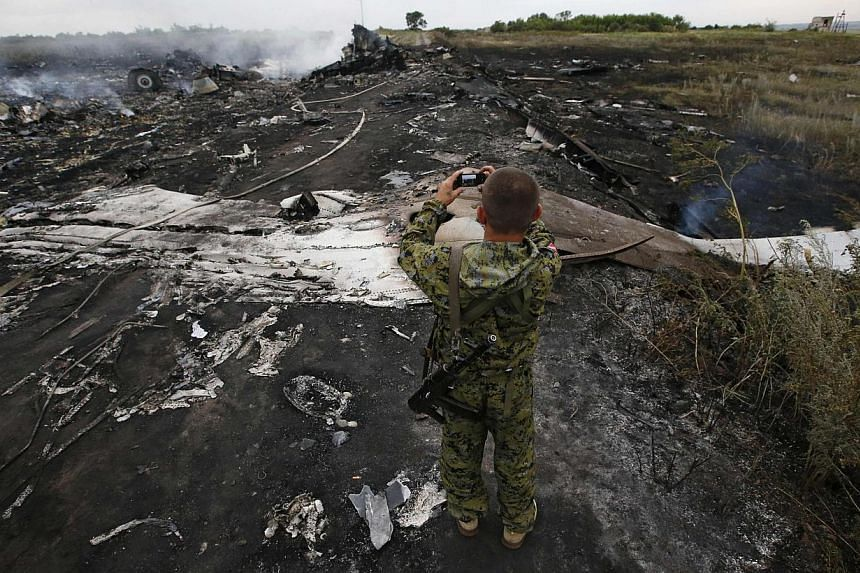 An armed pro-Russian separatist takes pictures at the site of a Malaysia Airlines Boeing 777 plane crash near the settlement of Grabovo in the Donetsk region on July 17, 2014. -- PHOTO: REUTERS