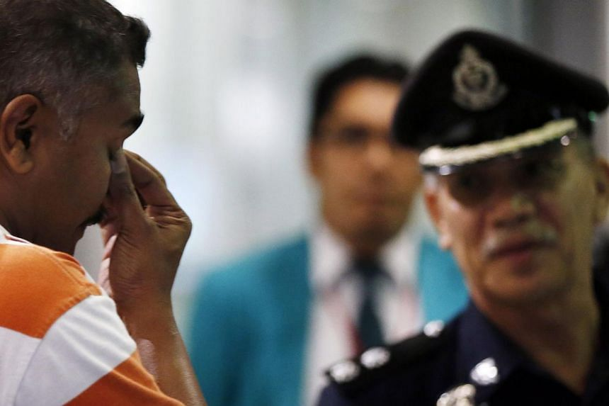 A man who said he believes he had a relative on Malaysia Airlines flight MH17 reacts in front of a policeman while waiting for more information about the crashed plane at Kuala Lumpur International Airport in Sepang on July 18, 2014. -- PHOTO: REUTER