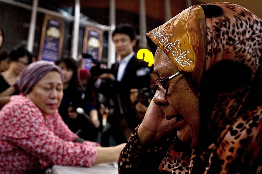 Relatives of people onboard Malaysia Airlines flight MH17 from Amsterdam react outside the family holding area at the Kuala Lumpur International Airport in Sepang on July 18, 2014. -- PHOTO: AFP