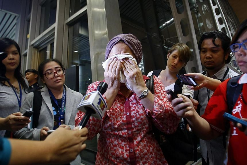 A woman, who said her name was Noraini and that she believed a relative of hers was on Malaysia Airlines flight MH-17, cries as she waits for more information about the crashed plane, at Kuala Lumpur International Airport in Sepang on July 18, 2014.