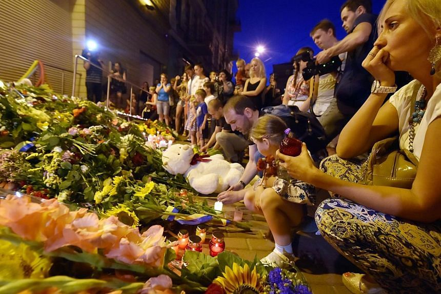 A woman looks on before lighting a candle in front of the Embassy of the Netherlands in Kiev on July 17, 2014, to commemorate passengers of Malaysian Airlines flight MH17 carrying 298 people from Amsterdam to Kuala Lumpur which crashed in eastern Ukr