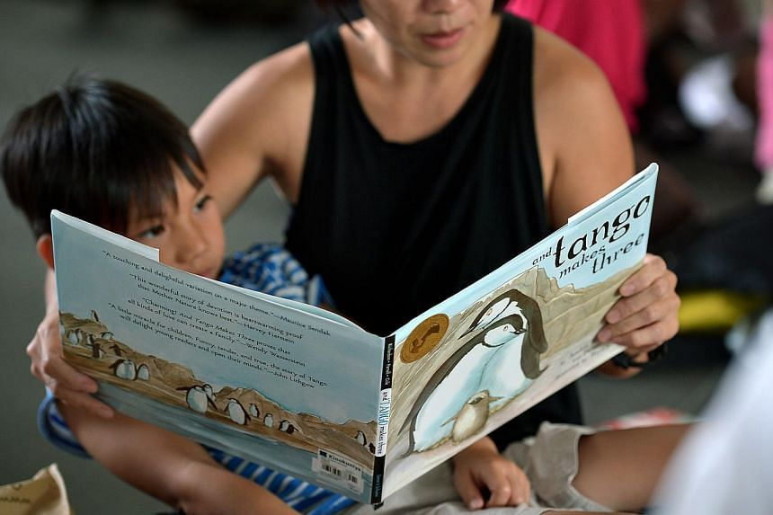 A mother reading one of the three banned books, And Tango Makes Three, during the Let's Read Together event, a reading event held in response to the National Library Board's (NLB) decision to pulp the titles. -- PHOTO: ST FILE