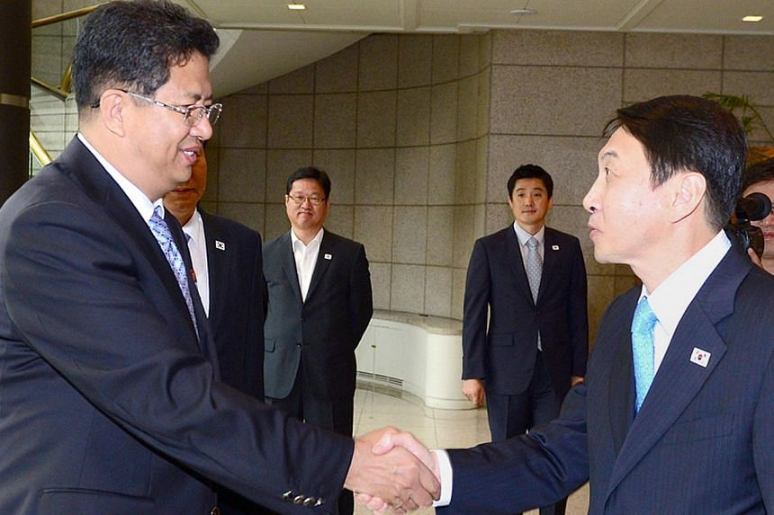 A picture released by South Korea's Unification Ministry shows Kwon Kyung Sang (right), secretary general of the Incheon Asian Games Organising Committee, greeting Son Kwang Ho (left), vice-chairman of the North Korean Olympic Committee, before their