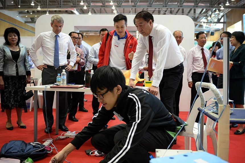 A Nanyang Polytechnic student toggles with his mobile robot as Deputy Prime Minister Teo Chee Hean (far right) and covering chief judge of mobile robotics Clarence Tan observe him, during a tour of the Worldskills Singapore competition held on 10 Jul