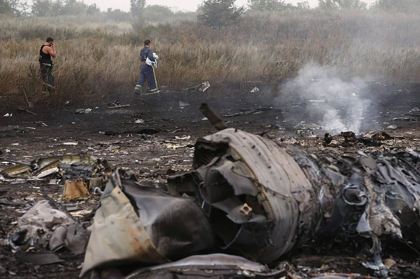 Emergencies ministry members walk at the site of a Malaysia Airlines Boeing 777 plane crash near the settlement of Grabovo in the Donetsk region, July 17, 2014. -- PHOTO: REUTERS