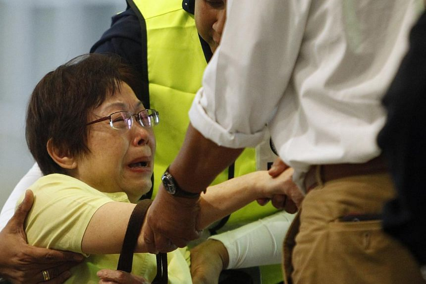 Malaysian Siti Dina weeps after seeing her daughter's name on the list of passengers on board Malaysia Airlines MH17 at the Kuala Lumpur International Airport in Sepang on July 18, 2014. -- PHOTO: REUTERS