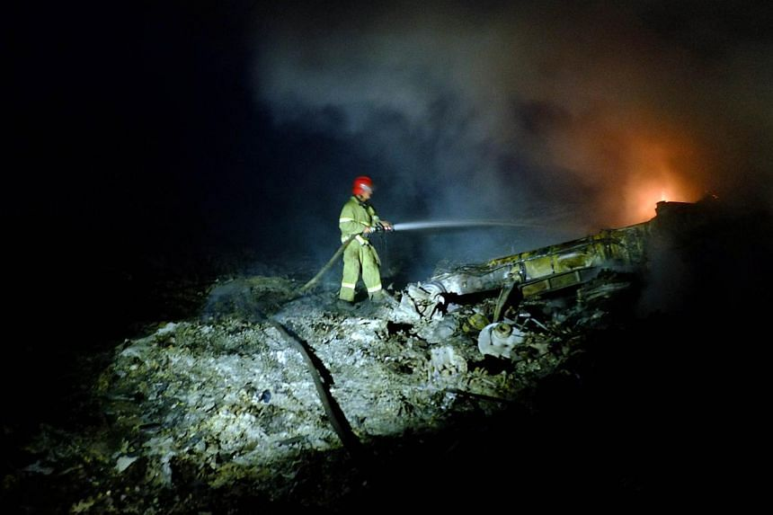 A firefighter sprays water to extinguish a fire, on July 17, 2014 amongst the wreckage of the Malaysian airliner carrying 298 people from Amsterdam to Kuala Lumpur after it crashed, near the town of Shaktarsk, in rebel-held east Ukraine. -- PHOTO: AF