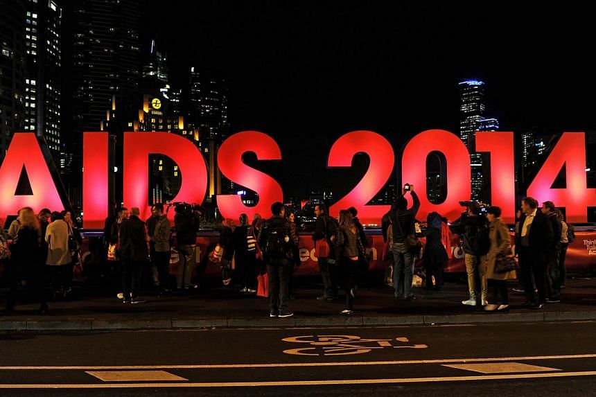 People gather next to a sign reading AIDS 2014 in Melbourne on July 18, 2014.Glen Thomas, a World Health Organisation (WHO) spokesman heading to the20th International AIDS Conference in Melbourne, was among the 298 people killed in the crash in