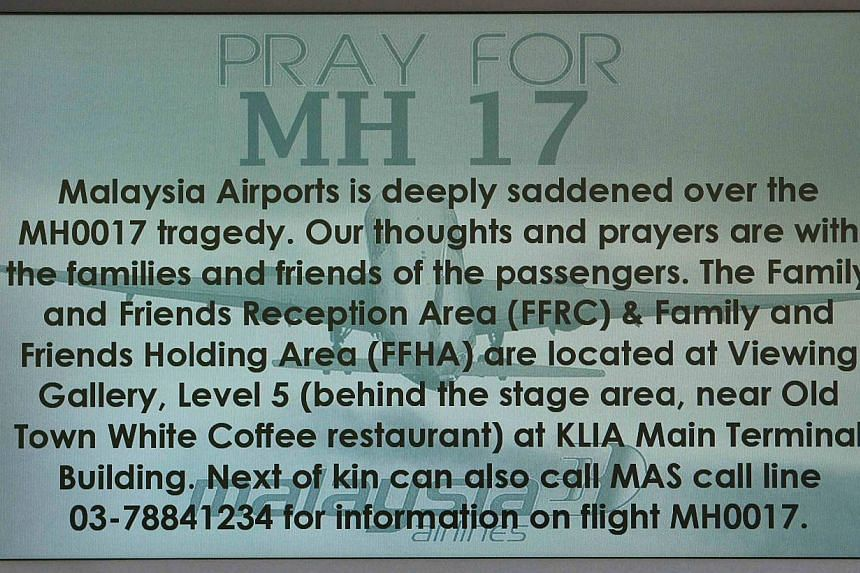 """A """"Pray for MH17"""" message is displayed on a flight information board at Kuala Lumpur International Airport in Sepang on July 18, 2014.The three Filipinos on board the Malaysia Airlines flight MH17 which was shot down over eastern Ukraine were a"""