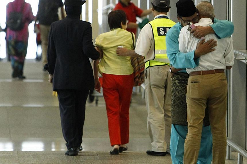 A man (in blue), whose family was onboard Malaysia Airlines MH17, consoles another man who had just arrived with his wife to receive confirmation that their daughter's family was onboard the plane, at Kuala Lumpur International Airport in Sepang July