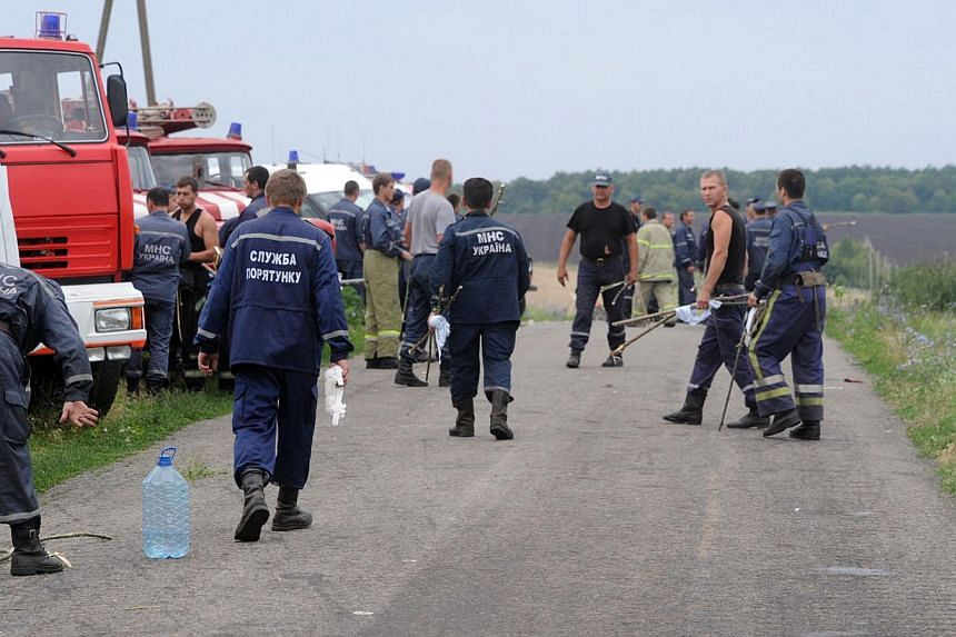 Rescuers stand on a road on July 18, 2014 near the site of the crash of a Malaysian airliner carrying 298 people from Amsterdam to Kuala Lumpur, near the town of Shaktarsk, in rebel-held east Ukraine.World leaders demanded an international inve