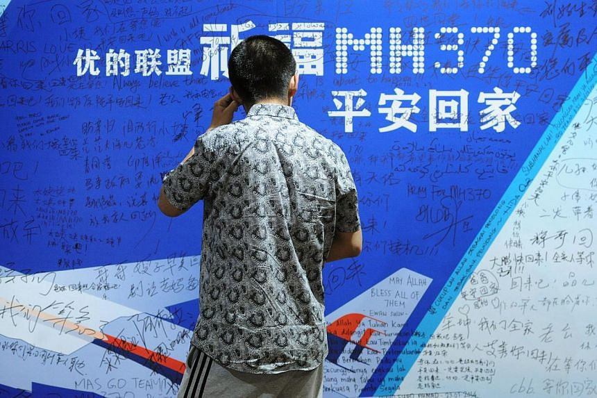 This file photo taken on March 30, 2014 shows a man looking at a billboard in support of missing Malaysia Airlines flight MH370 while relatives attend a meeting with delegates from Malaysia at a hotel in Beijing.Relatives of missing MH370 passe