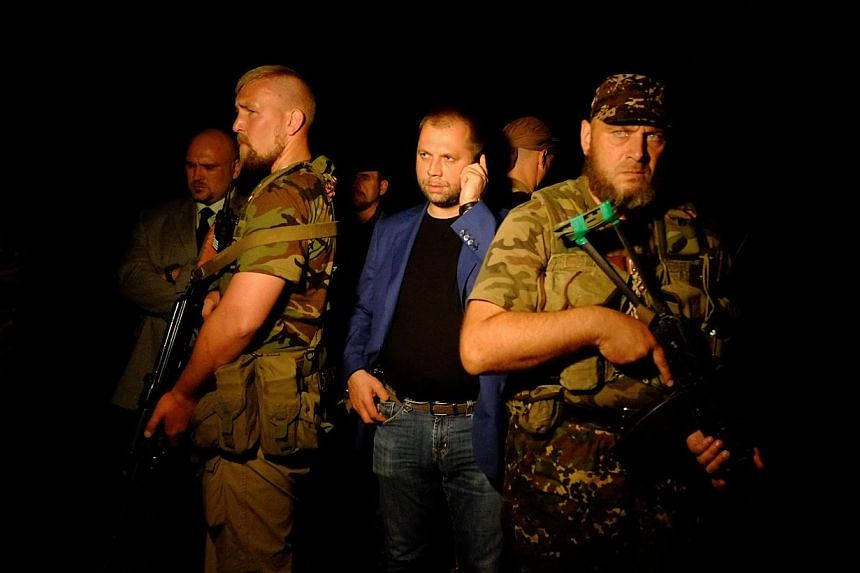 "Self-proclaimed Prime Minister of the pro-Russian separatist ""Donetsk People's Republic"" Alexander Borodai (centre) stands as he arrives on the site of the crash of a malaysian airliner carrying 298 people from Amsterdam to Kuala Lumpur, near the tow"