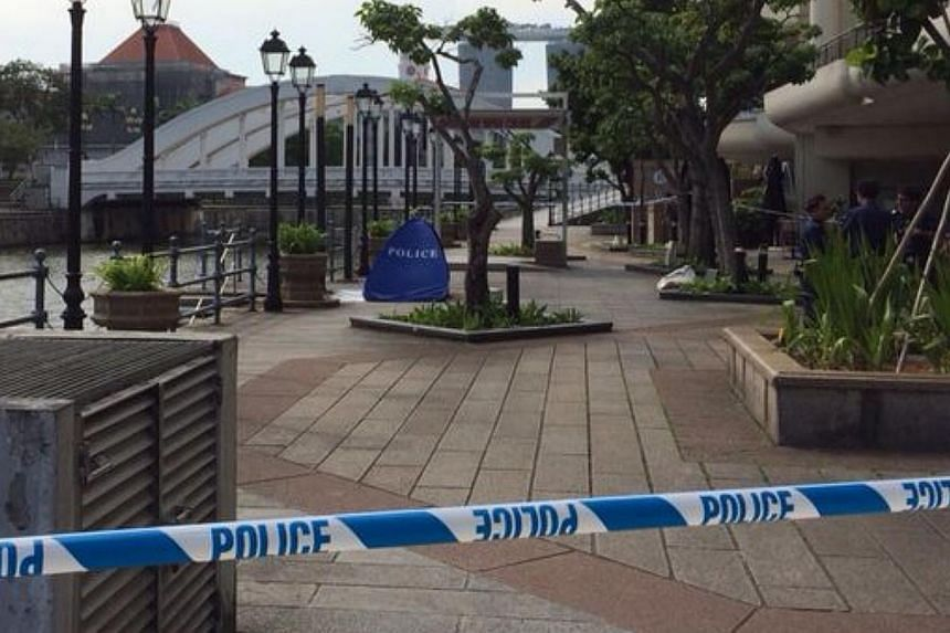 A police tent covers a body along the Singapore River at the Riverwalk, July 18, 2014. --ST PHOTO: ONG WEE JIN
