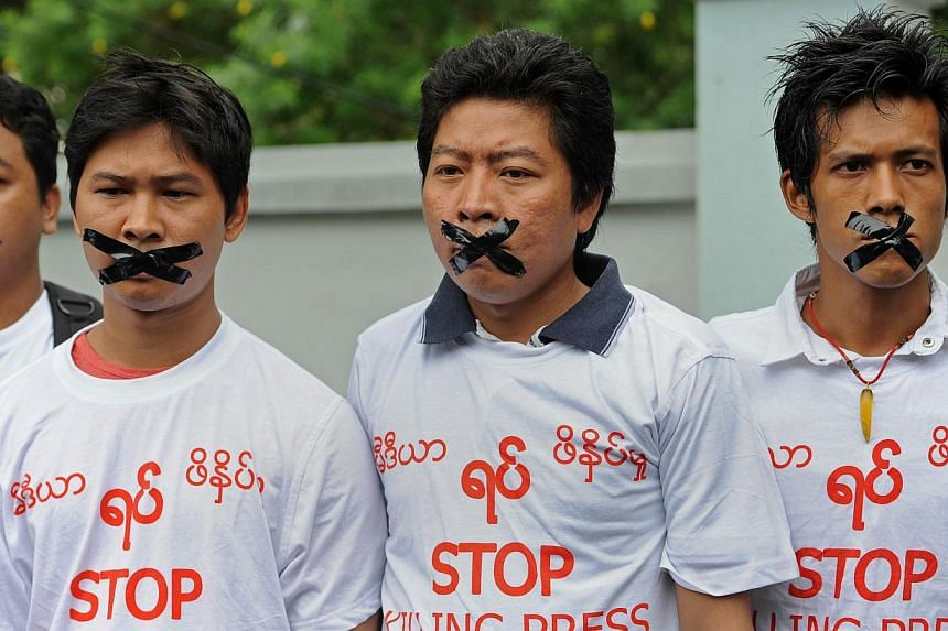 """Myanmar journalists wearing T-shirts that say """"Stop Killing Press"""" stage a silent protest for five journalists who were jailed for 10 years on July 10, near the Myanmar Peace Center on July 12, 2014. -- PHOTO: AFP"""