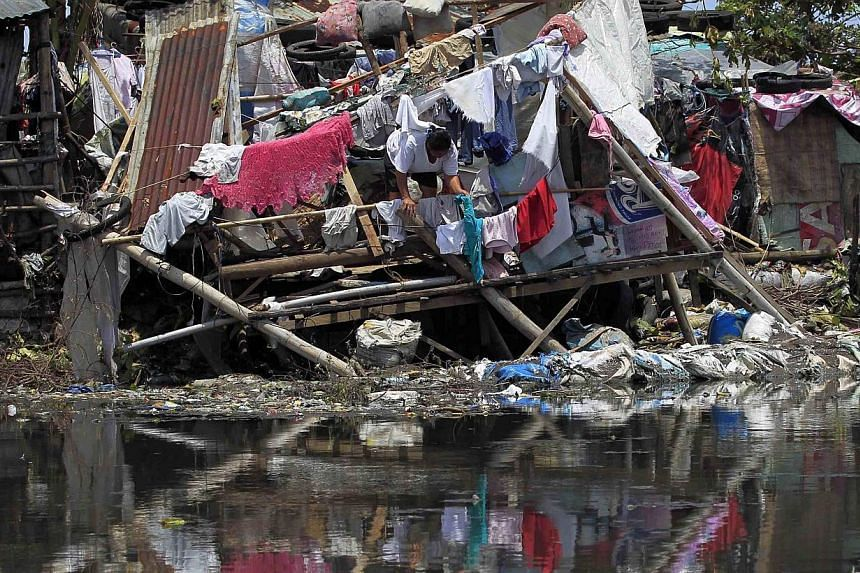 A woman hangs newly laundered clothes at a damaged house after Typhoon Rammasun (locally named Glenda) battered the town for two days, in Rosario, Cavite city, south of Manila July 18, 2014. -- PHOTO: REUTERS