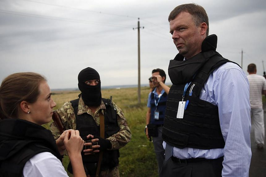 Organisation for Security and Cooperation in Europe (OSCE) monitors speak with a pro-Russian separatist at the crash site of Malaysia Airlines flight MH17, near the settlement of Grabovo in the Donetsk region, July 18, 2014. OSCE monitors were not ab