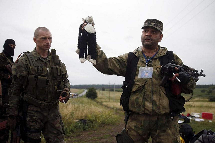 A pro-Russian separatist holds a stuffed toy found at the crash site of Malaysia Airlines flight MH17. United States President Barack Obama demanded Russia stop supporting the separatists in Ukraine after the downing of the airliner by a surface-to-a
