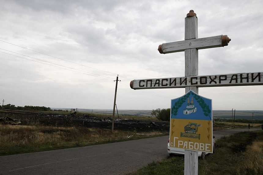 The village sign of Grabovo is seen near debris at the site of Thursday's Malaysia Airlines Boeing 777 plane crash, near Grabovo in the Donetsk region on July 18, 2014. -- PHOTO: REUTERS
