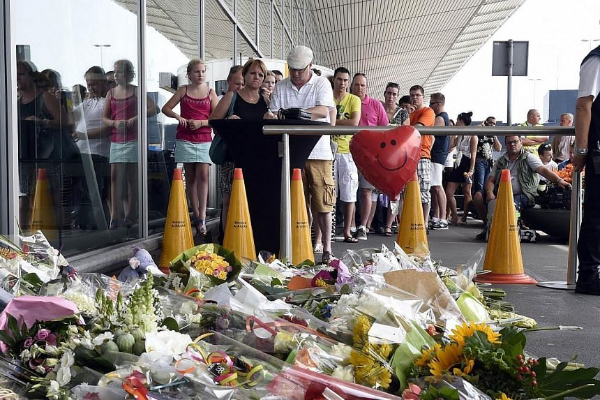 People sign a condolence register in front of Schiphol airport on July 19, 2014, two days after Malaysia Airlines flight MH17 carrying 298 people from Amsterdam to Kuala Lumpur crashed in eastern Ukraine.Relatives of the 192 Dutch victims of Ma