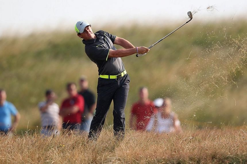 Northern Ireland's Rory McIlroy plays from the rough on the 12th hole during his second round 66, on day two of the 2014 British Open Golf Championship at Royal Liverpool Golf Course in Hoylake, north-west England on July 18, 2014. -- PHOTO: AFP