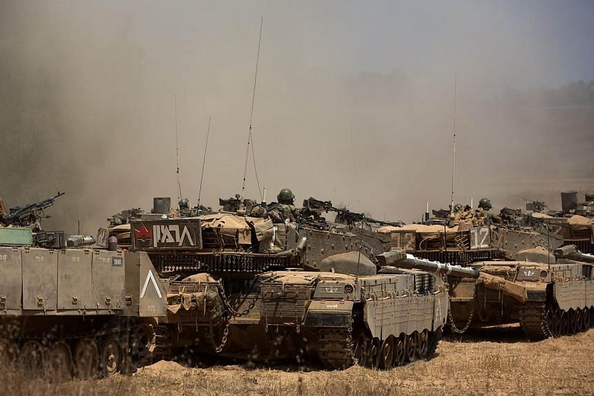 Israeli Merkava tanks roll towards the Israeli-Gaza border in an army deployment area on July 19, 2014. Nine Palestinians were killed in Israeli bombing across the Gaza on Saturday, July 19, 2014, afternoon, raising the toll in 12 days of violen
