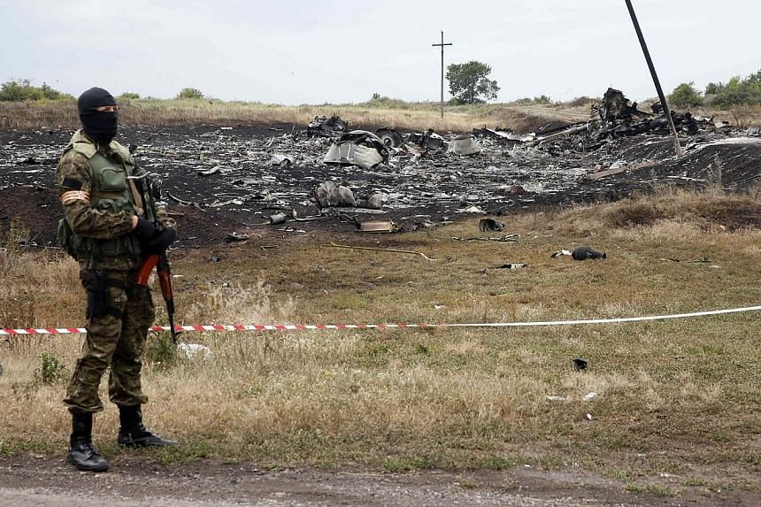 A pro-Russian separatist stands near a body at the crash site of Malaysia Airlines Flight MH17, near the settlement of Grabovo in the Donetsk region on July 19, 2014. The stench of death is now becoming almost unbearable over the wreckage of the