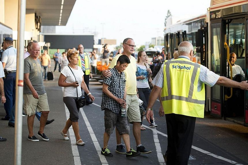 Relatives of passengers of Malaysia Airlines flight MH17 get onto a bus at Schiphol Airport near Amsterdam, the Netherlands, on July 17, 2014, headed for an unkown destination after they received additional information about the Malaysia Airlines pla
