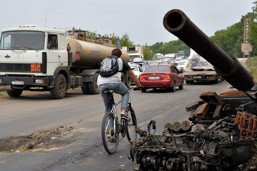 """A man rides a bicycle past wrecked tanks and armored personnel carriers (APCs) left by pro-Russia militants on a road near the eastern Ukrainian city of Slavyansk on July 18, 2014.Ukraine has """"compelling evidence""""that the crew which operated th"""