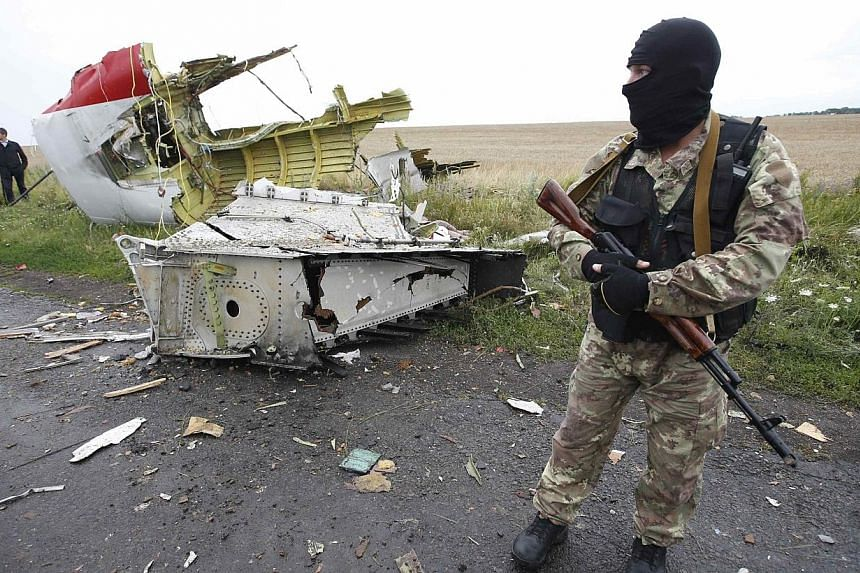 A pro-Russian separatist stands at the crash site of Malaysia Airlines flight MH17, near the settlement of Grabovo in the Donetsk region on July 18, 2014.Ukraine and pro-Russian rebels have agreed to set up a security zone around the crash site