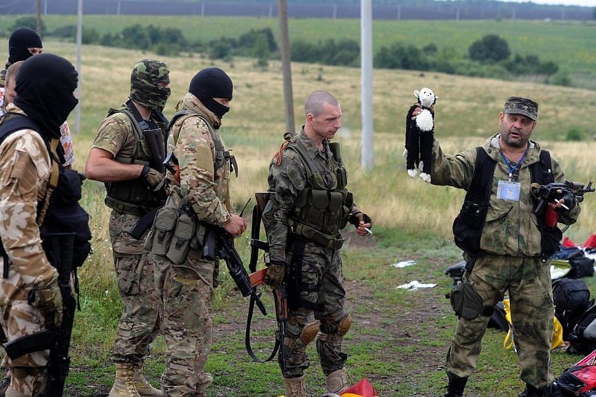 A pro-Russia militant holds up a stuffed animal as others look on at the site of the crash of a Malaysian airliner carrying 298 people from Amsterdam to Kuala Lumpur in Grabove, in rebel-held east Ukraine on July 18, 2014. Ukraine's government accuse