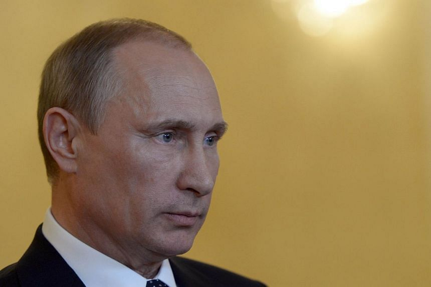 """Russia's President Vladimir Putin looks on while speaking with journalists in Itamaraty Palace in Brazilia, early on July 17, 2014.Ukraine accused Russia and pro-Moscow rebels on Saturday, July 19, 2014, of destroying evidence of """"international"""