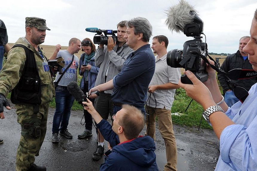 An armed pro-Russia militant attempts to stop journalists from accessing the site of the crash of a Malaysia Airlines plane carrying 298 people from Amsterdam to Kuala Lumpur in Grabove, in rebel-held east Ukraine on July 19, 2014. -- PHOTO: AFP